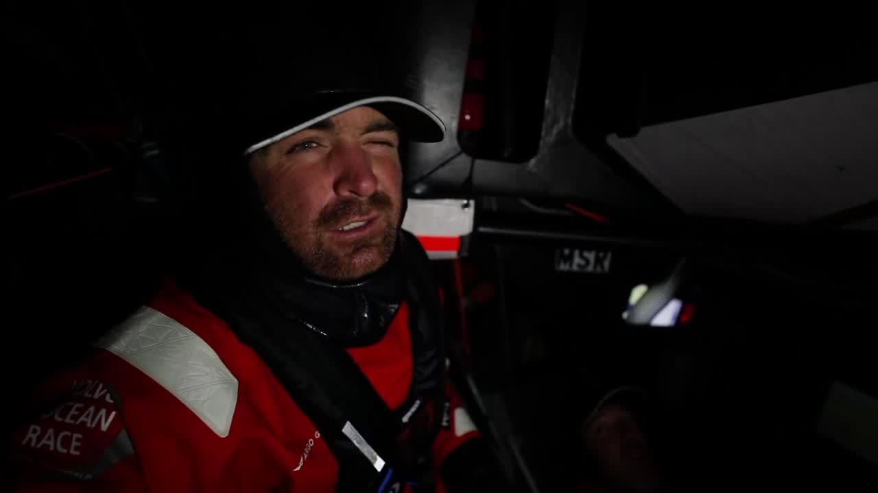 """Charlie, below, talks about how they've cleared the ice gate. """"We're in an ocean race. Now we have the whole ocean to sail around in."""" Mark, in the pit, talks about no more gybing. """"Well, no more gybing every hour."""" He trims something in in the pit. The crew shifts the stack from forward aft using the traditional heave chant: """"Two, Six!"""""""