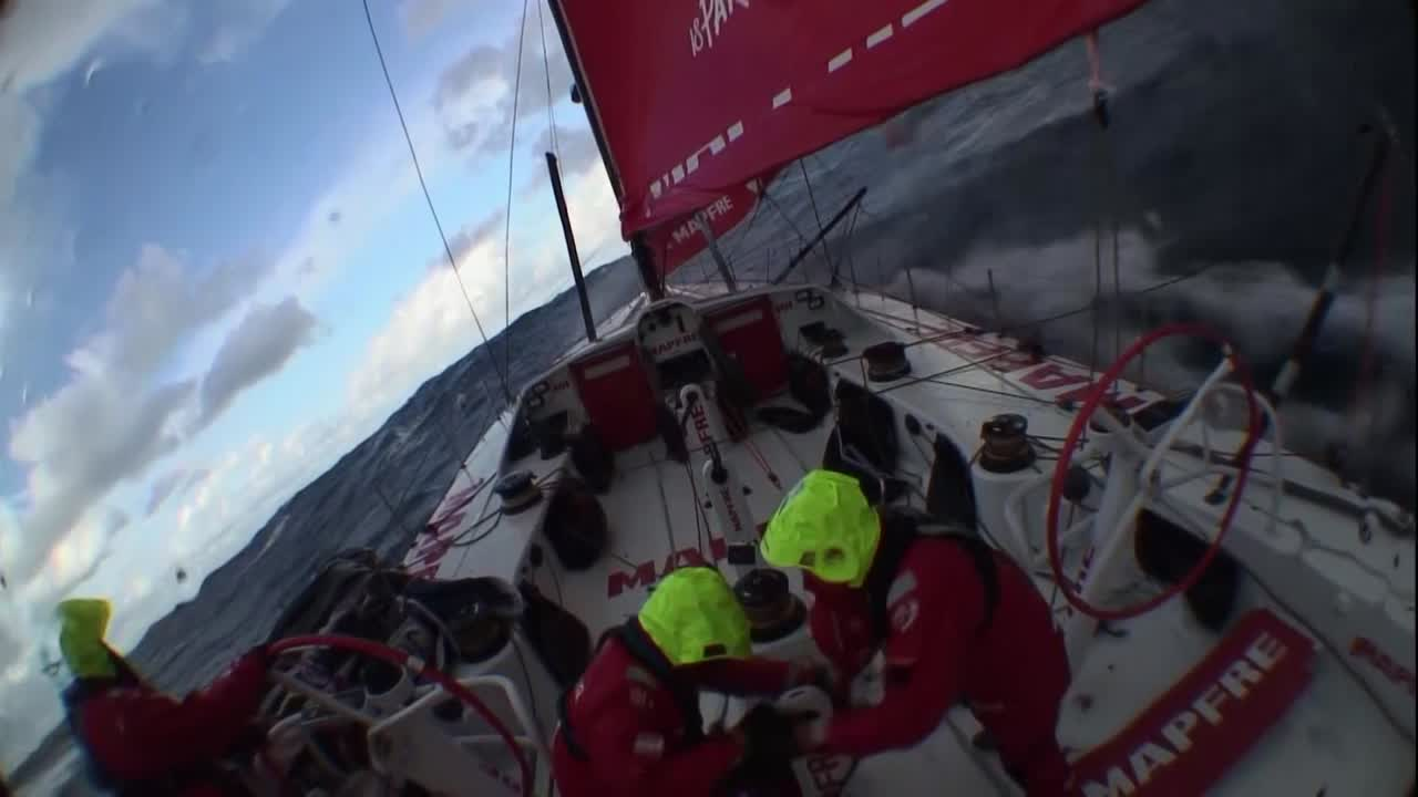 Crash cam / stern cam footage as MAPFRE surfs on port gybe with reefed main. Louis and Blair (I think? going by bits of name in Louis' case and bits of '77' visible on his back in Blair's case) are on the aft pedestal; a big wave wipes them BOTH off the pedestal.