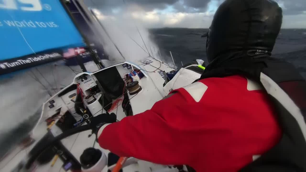 "Vestas sails fast on starboard gybe with a reefed main (I think?). Slomo washing machine shot from behind the helm. TJ, below, is eating. On screen title: Tom Johnson presents / A Christmas Story. Tom: ""Hello Sam, said TJ. There once was a boy trying to make it home for Christmas."" Stacey, eating below, talks about how they're 2 days away from Christmas. Stacey explains that she's not from that part of Australia, but a family is coming to see her. TJ talks about the big, cold low-pressure system that prevented them from gybing to get north. Shot on deck shows helmsman NOT standing on the helm platform, but instead on a stacked sail. Below, Sam asks Stacey, ""Motivation to go faster?"" Stacey: ""Yeah. We've been down in the cold too long, and we're pretty keen to get out of there... Any minute now it's gonna be balmy and warm."" Below, Tony eats, and explains that real Christmas for him is getting away with the family for a summer holiday. Stacey jokes that this isn't warm. Tony exhales so you can see his breath. TJ keeps telling his Christmas story, trying to get there to see his family on Christmas. Father and mother; his sister he hasn't seen for 3 years. And his niece Lucille that he's never even met. Talks about that being a hard thing about his job: Always moving. Charlie talks with Simon (off camera) about how they should do stealth mode now, becaue once MAPFRE is within 200 miles of the finish it will end. TJ talks about stealth mode. Charlie talks about how they've decided when to gybe, strategic consideration with Brunel. TJ: ""TJ's storytelling voice... You'll find out how the story ends in a couple of days. Hopefully it's a happy story."" Tony on the helm. TJ: ""He's bringing his sled. A big sled, Vestas Wind."""