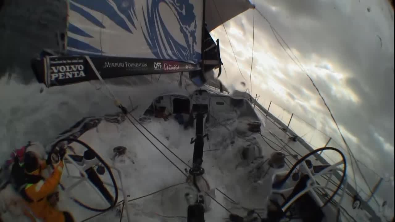 "Crash cam, stern cam. We see TTToP surfing down a big wave on port gybe. They get too low, bury the bow, pop the rudders out, and the boat gybes accidentally to starboard. They immediately grind in the main (good; helped to keep the rig in), get the keel across (presumably), then tack around onto port again. Liz, below, explains what happened. Bleddyn describes what happened. Frederico says that was his first time doing that in a Volvo 65 (which gets a laugh). He describes what it was like down below. Dee says it was inevitable, probably, but things got sorted out. ""A few wide eyes."""