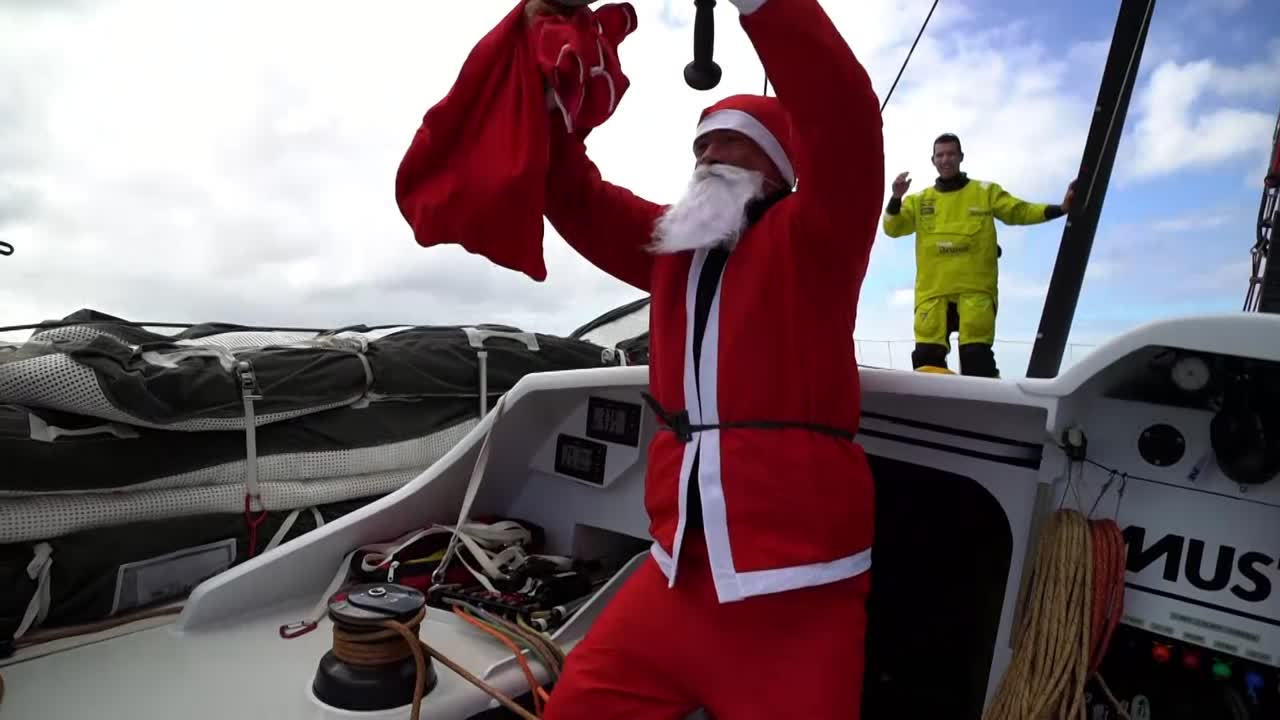 "Bouwe comes out of the cabin into the cockpit wearing a Santa Claus costume. He's holding a sack and banging on a teapot. Carlo watches from the shrounds. Santa: ""Ho! Ho! Ho! Merry Christmas!"" Santa gives a present (a card?) to Capey. Capey: ""It doesn't look like I can eat this."" Peter watches from the helm. Peter gets a (poorly wrapped) present. Abby gets a present (hers actually looks pretty nice). Santa gives Annie one present, then swaps out a different one and gives hers to Alberto. Louis, poking his head up from below, gets a ""baby"" one. Santa walks to the bow, then back. Kyle emerges from the cabin rubbing his eyes. Louis puts on reindeer+Santa hat sunglasses. (Assuming that was his present?) Santa passes out the final gifts: Cookies. ""Sharing, sharing..."" Santa removes his beard to enjoy a cookie. Carlo talks to Ugo: ""You really miss out on the special days doing this race. So it's nice to be able to celebrate Christmas with Santa on the boat."" Below, at the nav station, Santa/Bouwe types at the computer."