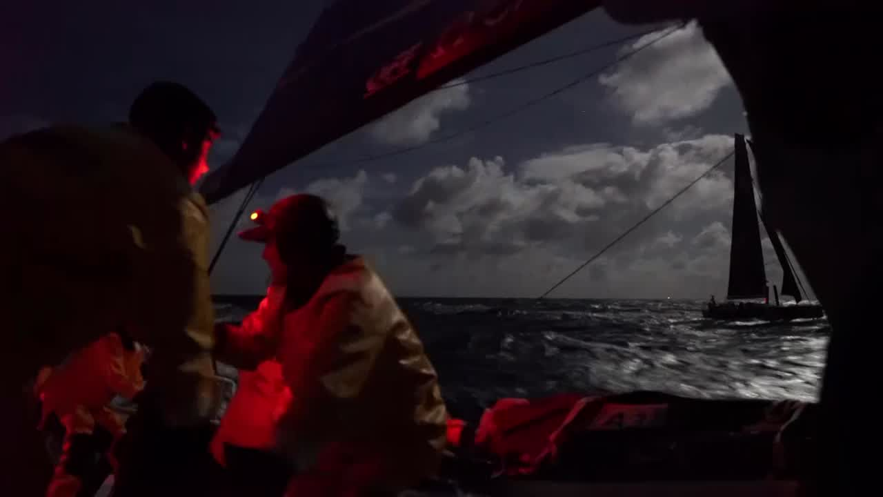 Night shot of the cockpit. Crew on the pedestal grinding with red headlamps on while the full moon illuminates clouds and the ocean behind them. Another boat can be seen a hundred yards away on their port side; TTToP gybes. Looks like the gybe they made around 1445 on 2018-01-02, which would mean that's Scallywag next to them. We see Scallywag sailing in the moonlight on their port side. On their starboard quarter we see what I think is South West Island with a light on it (FL 4 sec?).
