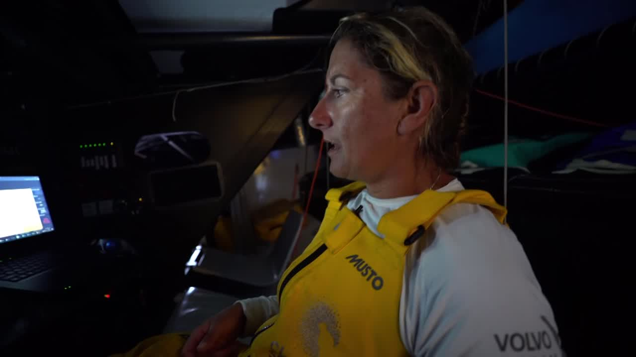 "At the nav station, Dee talks about deciding whether or not to gybe. Most of the boats have headed offshore. Brian [Thompson] has gone on deck to look at how things are. We see Brian talking to Dee through the companionway. ""It's just silly to go this way."" Dee wakes up people below: ""Time to gybe."" Liz: ""I love the gybing what do you mean I don't like the gybing I love the gybing."" Dee, at the nav station, talks about how it's harder to be with everybody rather than sailing on their own. But it's good; morning two and they're with the whole fleet."