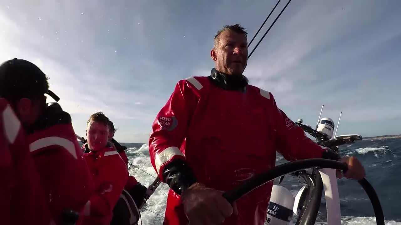 """Scallywag reaches on starboard tack with J1 and J3 in fairly flat water. TTToP is 1/4 miles away, ahead and to windward. I think this is probably from the afternoon of the first day of the race, around 2018.01.02 08:48:50 UTC, when they had exited Port Phillip Bay and were heading SE along the coast. Witty steers and wipes spray from his face; the low coastline is visible to leeward. Witty talks about what's coming up. """"Scallywag's in reasonable shape."""" Points out the other boats around them. Washing machine shots in the cockpit. Shot of the stern with the sunset. Witty talks about strategy, not reacting to the other boats. But seeing the other boats around them is reassuring. """"Pretty sure we're going the right way then."""" Shot of Libby with a tablet. Grant, panting: """"I'm slightly out of breath from grinding. I've been pushing electric winch buttons for the last 15 years. It's much easier. But this does keep you warm."""" Witty: """"Should have had full crew numbers from day one I think. Certainly makes it a lot easier. Trystan's a big strnog guy, which helps. Warry's been doing a good job driving, Libby seems to be a bit of a class act so far, so it's all good. Talk to you tomorrow. See where we are tomorrow. MIght change my mind!"""" Gybe in the cockpit. Shot of MAPFRE to leeward with the sunset behind them."""