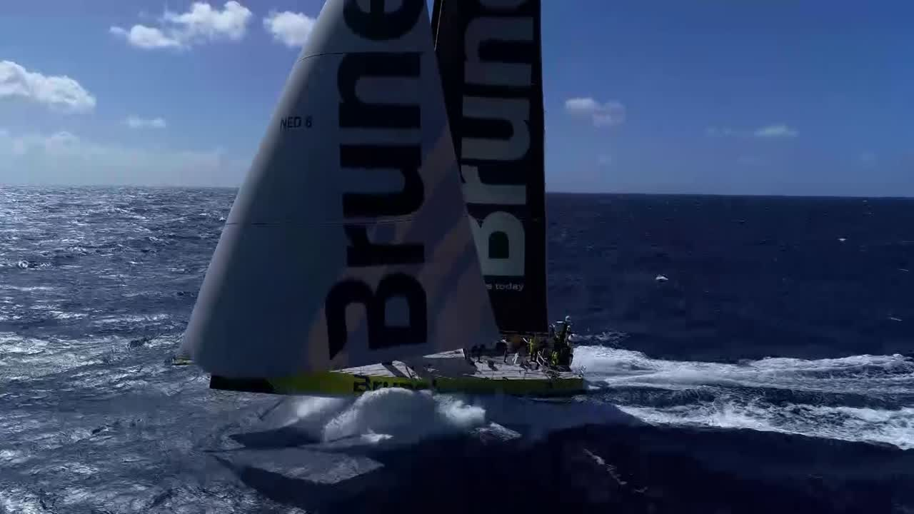 Great drone shots of Brunel triple-heading on starboard gybe. Good overlapped audio from the boat. On the stern Bouwe talks about how they're not as fast as the other boats in the middle wind ranges. Maybe trimming, driving. A bit of an Achilles heel. Losses less than on the second leg. Managing to hang on; hopes the gap doesn't get any bigger. After the Solomon Islands will be other conditions and opportunities. Slomo wake shot with interesting cascading-curtain-of-water effect.