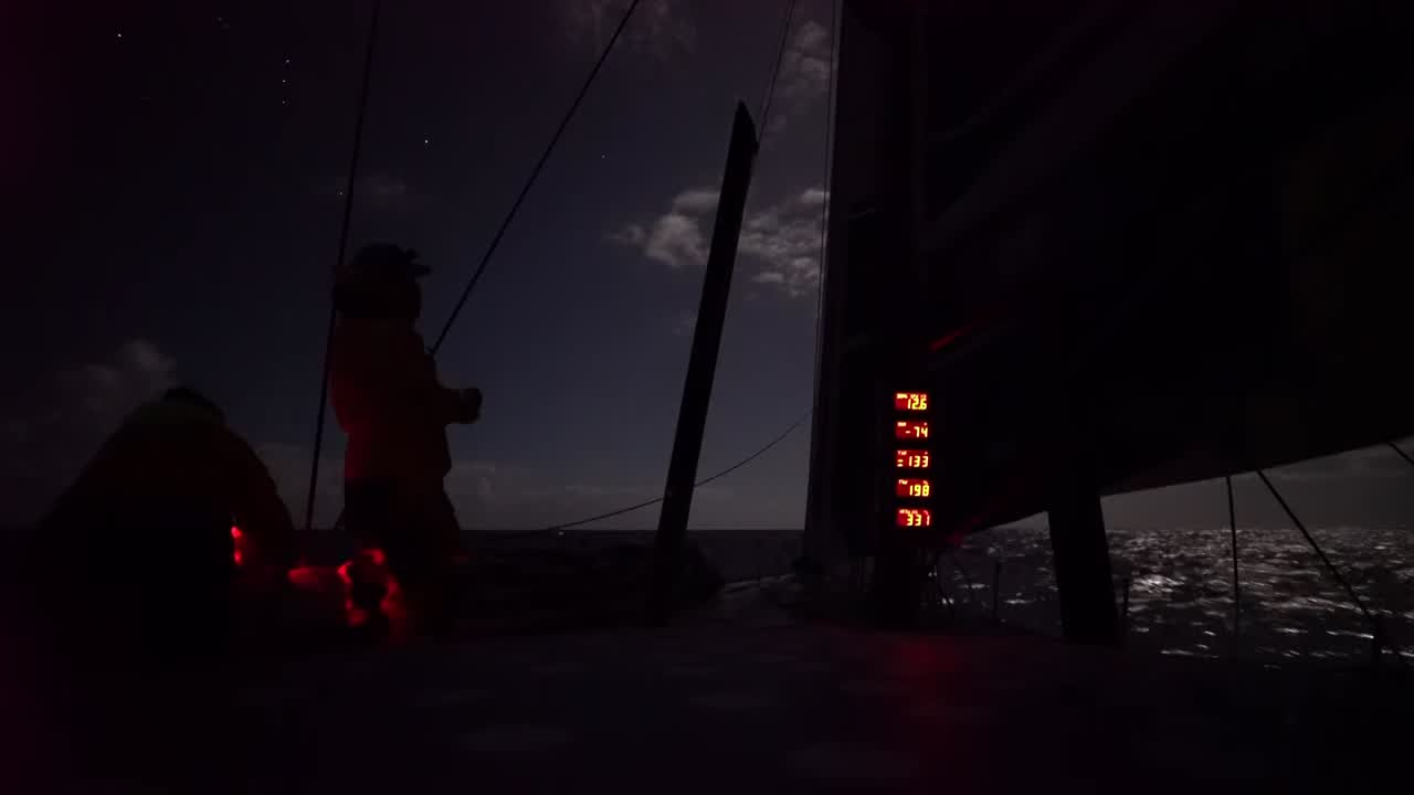 "TTToP sails at night with the full moon behind the sails. MAPFRE sails a few hudred yards away, below and slightly ahead of them. MAPFRE appears to be sailing slightly higher; they discuss that they might end up in their bad air. In the dark, Brian (Thompson), who's on the pedestal, explains the current situation to Brian (Carlin): In the middle of the Coral Sea, slightly north of Lord Howe Island, in a match race with MAPFRE and Vestas. He explains that it's helping them tune up and sail faster to be sailing next to the two boats. Liz, on the helm, talks about how it's pretty intense sailing close to the two boats. ""Brian's down there calling relatives and we're just trying to match them."" Dee, at the nav station: ""Intense but exciting."" Elodie, on the rail with binoculars, looks ahead and to port. ""They look really loose on everything, that boat."" She talks about how interesting it is that MAPFRE is sailing relatively high, while Vestas is managing to soak down without losing too much speed. ""We're a bit the cheese in the sandwich here."" Martin, looking to starboard with binoculars: ""They've got sails in front and behind the shrouds as well."" (Think he's talking about the stack.) Bernardo, trimming: ""I'm smiling becuase I'm enjoying it. I don't have any reason not to smile."" Dee, at the nav station: ""I'm so proud to see these guys develop before your eyes... I'm a proud mum."" Drone shots of TTToP sailing at sunrise on port gybe. Crew is shifting the stack. MAPFRE is visible ahead and to starboard."
