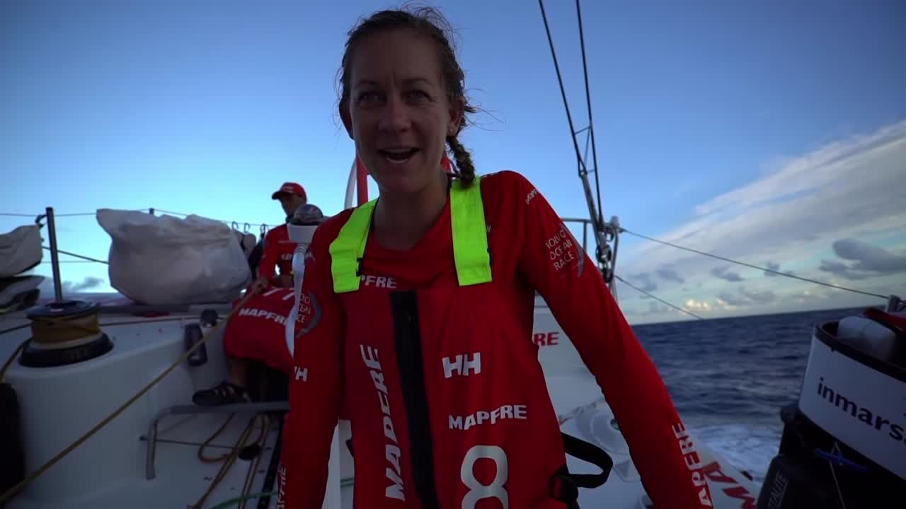 "Sophie, on the aft pedestal, summarizes where they stand. Have gained back on the two lead boats, AkzoNobel and Dongfeng. Blair, trimming, talks about how they caught sight of the other two boats that morning sooner than they expected; MAPFRE got some good pressure and the other two boats got stuck a little too low, such that ""Vestas and us caught them a little bit."" Now into tradewind sailing. Now they're in the same wind so it's all down to boatspeed. Maybe there will be more clouds at night that allows for bigger gains and losses. Sophie: ""I think we're all pretty excited to be back at the front of the fleet."" Willy stands at the shrouds looking up at the sails. Shot of Dongfeng ahead of them. Támara looking forward. Sunset. A bird (a Brown Booby, I think) flies above the masthead. Pole shots of the rudder, the wake."