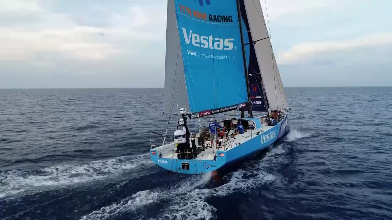 Drone shot of Vestas reaching in 10 knots of breeze with MAPFRE visible several miles away, ahead of them and to leeward. More drone shots.