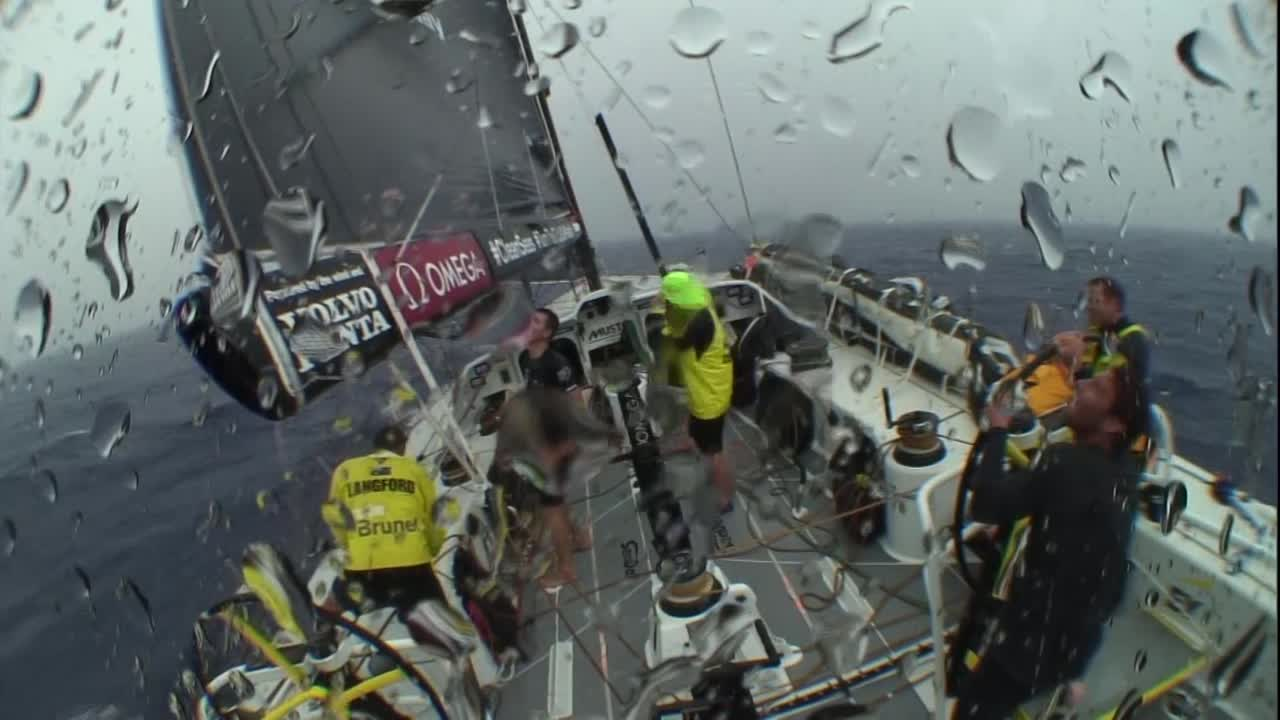 """Crash cam footage from the stern cam: They're sailing in light wind and heavy rain in a squall. There's a flash of lightning and a loud crash. Rome, on the helm, jumps off the helm platform to crouch down in the stern. They laugh. Rome: """"Holy shit!"""" Below, Kyle and Sam watch the footage on a laptop. Kyle: """"He's very easily scared, that Rome-y. You'll walk around a corner and he'll jump. Very easily frightened."""" More of them watch and laugh. Rome: """"Shat my pants it was so close."""" Sam, on deck, talks about having the lightning strike quite close, feeling the static through their bodies. """"Bit close for comfort. Lucky we got out with the instruments unscathed."""" Night shot of distant lightning. Shot of the mast instruments at night. Bouwe at the nav station. Closeup of the compass dial. Slomo wake shot. Shot of passing Ghupuna; drone shots of passing Ghupuna. Sally, with a Scopolamine patch behind her right ear, looks at land. """"Nice. It's a little bit of something besides blue water."""" Jens: """"It's always nice to see land. It's only halfway, looks good. Have a couple of boats we want to catch."""" Yann, to Bouwe on the helm: """"You like the green you're seeing, or...?"""" Bouwe: """"No. I like more the beach, actually. I'm more a beach man."""" Shots of the island. Abby and Sally working in the pit. High drone shot of Makira behind them."""