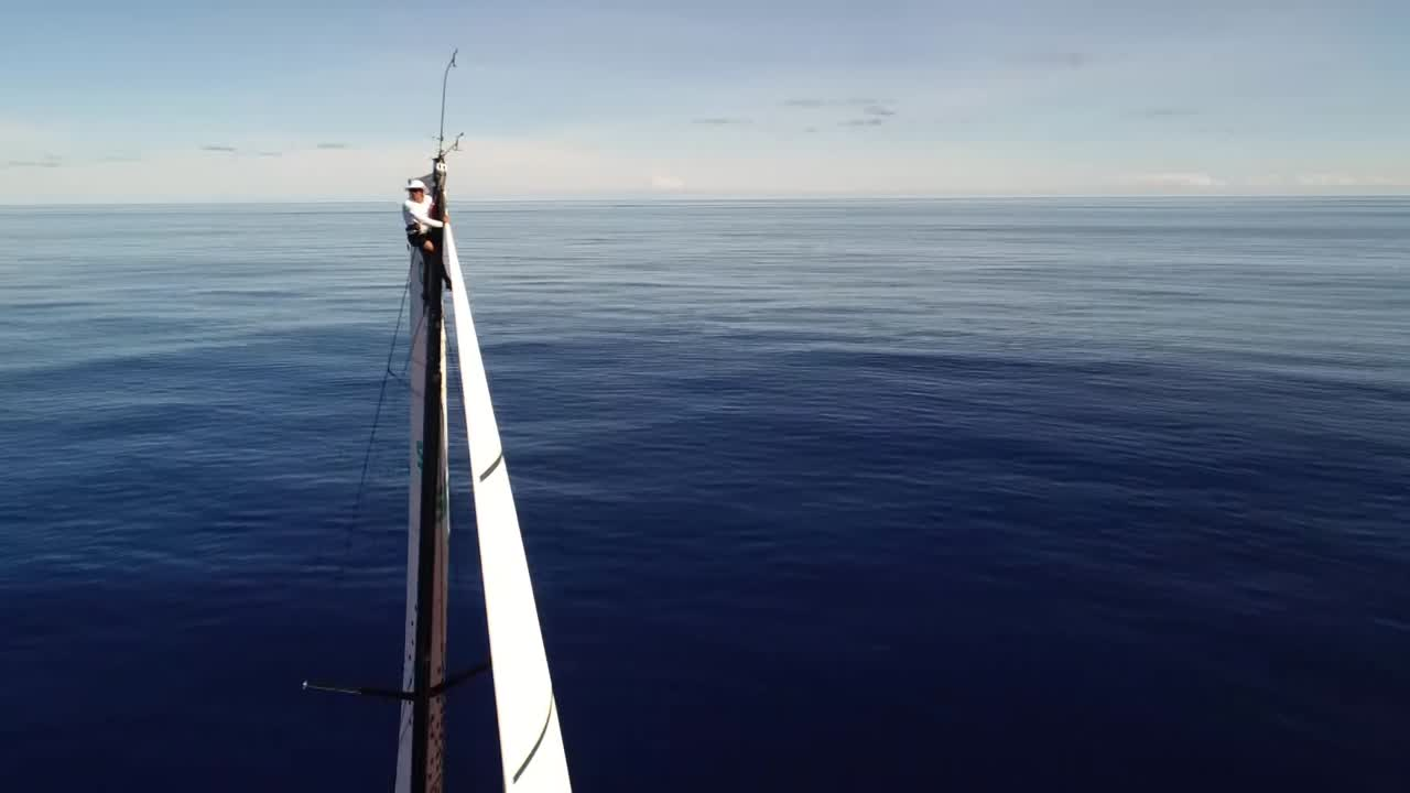 Drone circles the masthead. Someone (not Liz, I don't think, but not sure who) is there scanning for wind. Drone shot from high overhead looking down on the deep blue sea beneath the boat.