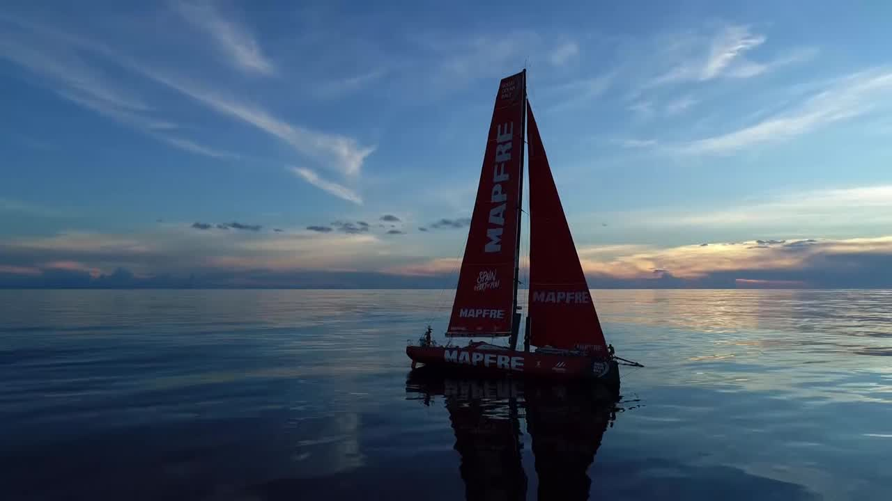 We see Ugo launch the drone, which flies away. MAPFRE drifts on a glassy ocean. Very low-altitude drone shots that circle the boat, first farther away and then close.At one point we see a distant competitor ahead and to leeward. We see Sophie's silhouette on the bow as they hoist the J1 (or maybe it's just that the J1 is set with a loose halyard for drifting/windseeking conditions).