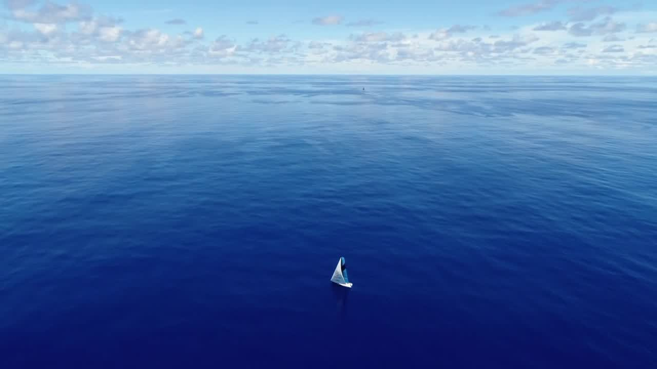 "High drone shot of Vestas on a blue ocean with very little wind. AkzoNobel is visible a few miles away to windward. Mark, on the wheel, points to three boats to weather. We see a shot of them; left to right: AkzoNobel, Dongfeng, MAPFRE. Phil and Hannah lie in the shade of the main. Phil: ""It's probably a really nice comfortable 50 degrees downstairs, and about 47.8 out on deck. Sea temperature of 32 degrees, so it's just a pleasure."" Nick and Mark in the cockpit look to weather, talk about the other boats getting the wind first. Sam, to Nick: ""What do you know, chief?"" (On the helm, Mark bangs the wheel.) Nick: ""Um. Mark's scaring me."" Below, TJ talks about how hot it is and points out blisters forming behind the paint/surface coating (?) on the starboard side due to the sun. Talks about needing to drink another bottle of water. We see a shot of a pad in the foreward sail locker where someone has been sleeping, drenched in sweat. On deck, Stacey sits near the mast in an eerie silence. ""We're barely moving and we've got four other boats all within eyeshot of each other."" TJ looks through binoculars at AkzoNobel, describing what sails they have up: ""They're not furled because their zigzags are lining up with the jib. So it's the J1 or the Code 0."" They joke about the routing, it taking 3,000 years to reach their destination. Tony, from the wheel, calls out, ""If we're out here for 3,000 years we'll have a few typhoons to deal with."" SiFi walks forward, talks about the GPS mark time being 1,360 days. Nick: ""That's Instagrammable."""