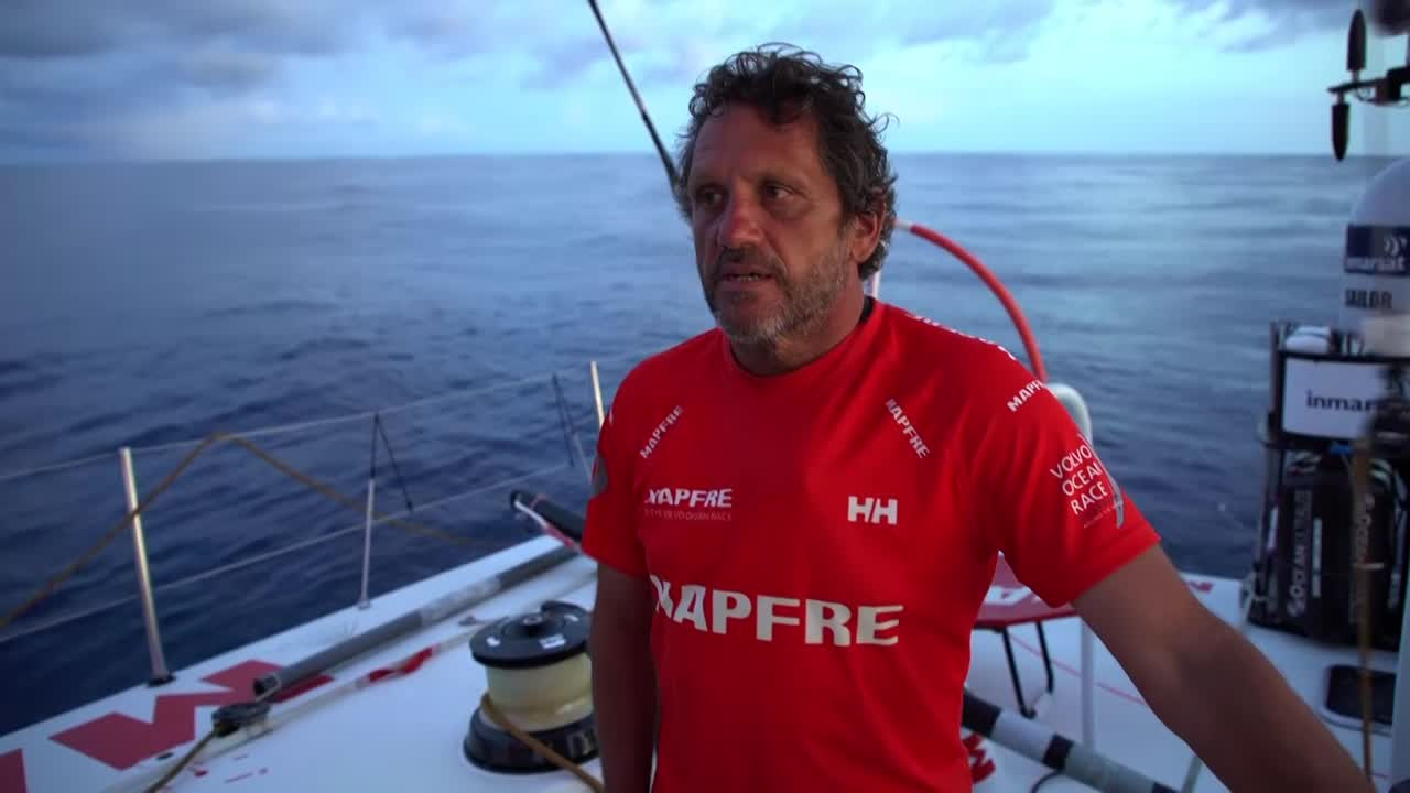 Joan, in the cockpit, talks in Spanish as MAPFRE flops with no wind under cloudy skies. Rain; slomo of Sophie, Joan, Xabi grinding in the rain. Sophie and Támara on the bow in the rain. Moving fast in the squall, and... becalmed again. Crew looks for wind; Xabi discusses it. Blair hauls the clew aft.