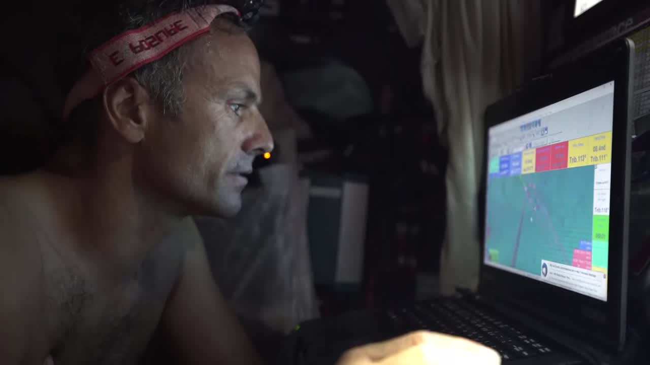 "Franck, at the nav station, looks at routing software and talks in French; I caught ""Vestas."" He talks about it over his shoulder to Jack (?) in the bunk behind him. Then he talks to Charles. On deck, Charles talks about how they have just taken the lead, or are in the same position as Scallywag, ""but we prefer our position for the future. We should be the boat with the most wind for the next few hours."" Hopes to have left the doldrums and to be the first to catch the tradewinds. A booby flies over the masthead."