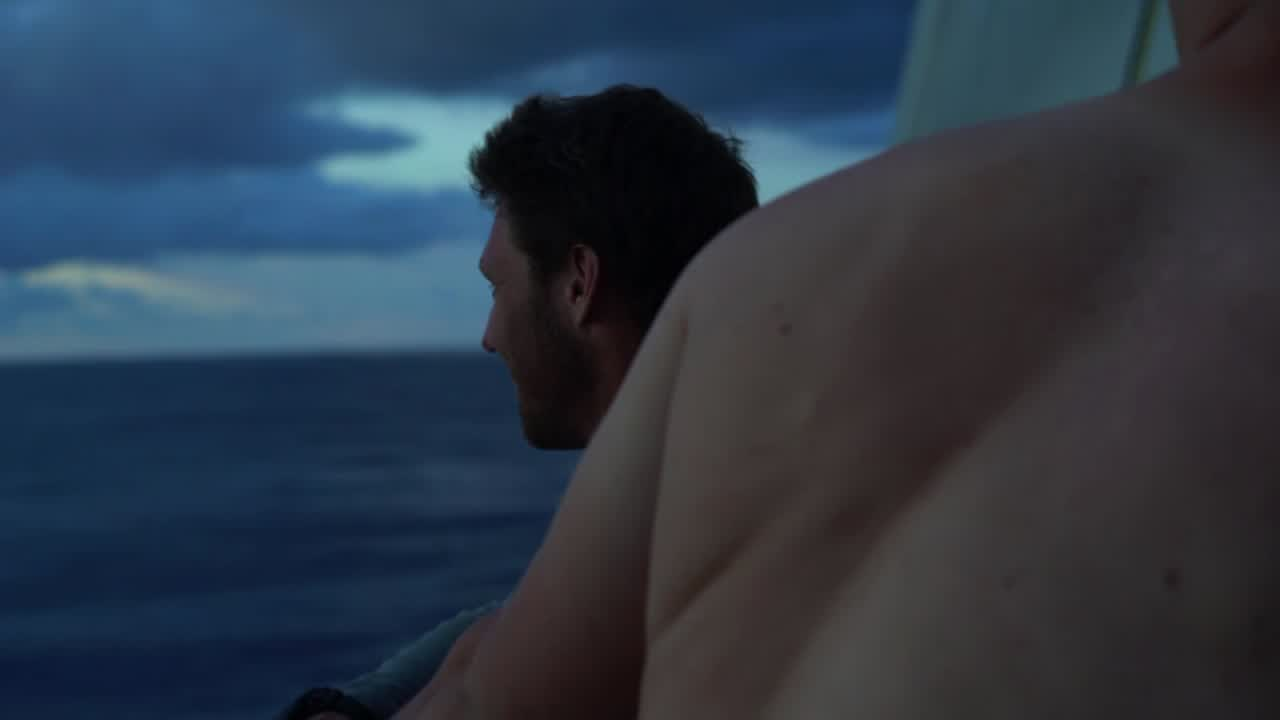 """Rome points out MAPFRE on the horizon. Bouwe steers in the dusk. They sail in the darkness in light wind. Sunrise astern. Very low-altitude drone shot overtaking them on a glassy sea. Drone shot circling them high overhead. Flopping in the morning sun. Jens points out more breeze ahead. Sailing in a building wind. Shot of the plot. Bouwe explains that a big rain cloud appeared, and they kept going in the same direction, while the two nearby boats put up a jib and sailed higher. And then Brunel parked up under the cloud, and the two boats behind saw that on AIS, and the two boats (especially MAPFRE) made a lot of distance on them by pointing higher. Now TTToP is just to leeward of them. """"Just a matter of keep pushing hard and never give up. The race isn't over until the finish"""" (he says through slightly clenched teeth)."""