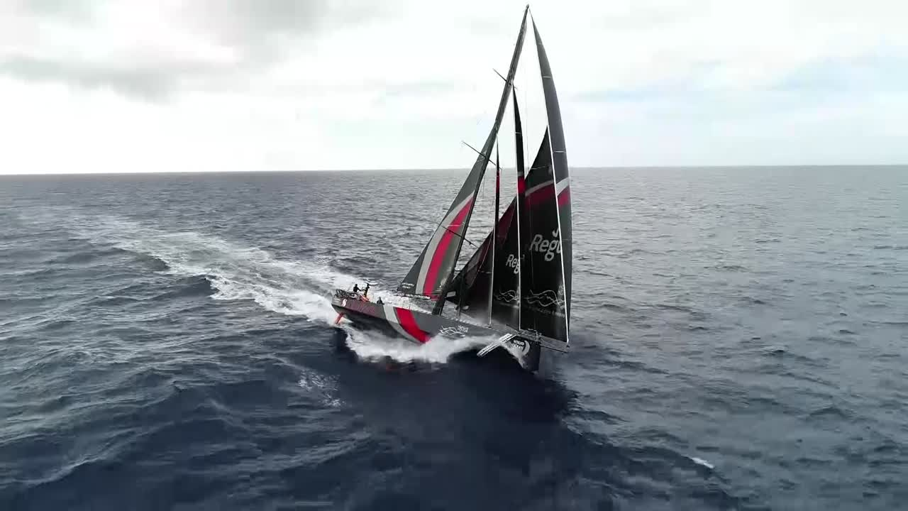 "High drone shot of Scallywag sailing fast, triple-heading on starboard. Slomo washing machine. Grant, trimming in the cockpit: ""When David Witt says to me, 'Come and sail the Volvo 65 with me', I said, 'Oh, that sounds like fun. Are they very wet?' He said, 'A little bit.' 'Are you sure?' He said, 'Wetter than anything you've ever sailed in your life.'"" Slomo washing machine shots in the cockpit. Ben on the helm. Drone shots."