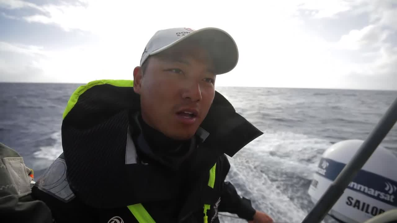 Horace, standing on the stern as they sail fast on starboard, talks in Mandarin (I assume). He gives a thumbs up. Shot of him steering, then trimming.