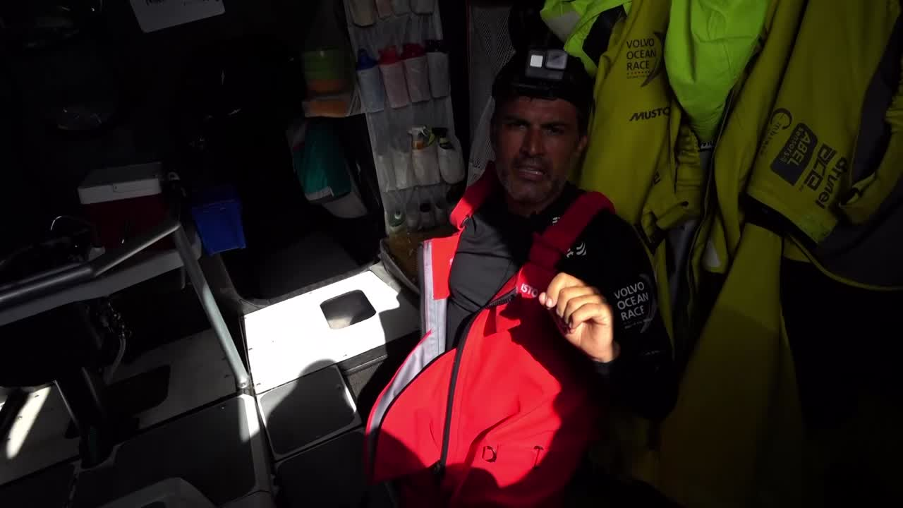 "Yann, below, explains that he's going to try to fly the drone, even though there's a bit of water on deck and it's pretty windy (about 18-20 knots). There's a reef to windward, and he's going to try to get the reef in the drone shots. (Not sure who's videoing this, but you can see their shadow in the shot.) He's getting everything ready there, then he'll give the drone to Jens, who will take the drone to the stern and launch it. Yann stands in the hatchway, being filmed as he talks to someone on the stern. ""Whenever you think it looks okay you come and pick it up, with the camera looking... this side [he gestures toward the stern] so that it doesn't get any spray on the lens."" Jens comes and takes the drone; carries it aft through the cockpit. From the mast cam we see him take it onto the stern. Then we see Yann's GoPro (really Garmin) head-mounted camera view as he walks toward the stern with the drone controls. We get a shot over Yann's shoulder as he talks to Jens. We see the drone launched, then see the launch again in slomo, then see the drone's view as Jens releases it and salutes it as it flies away. We see the GoPro (Yann-cam) view of the person videoing him, who I think might be Kyle? Yann: ""Now it's just a matter of doing some, uh, nice picture... Shouldn't be too dangerous if I don't get too close to the boat."" Shots of Yann on the stern operating the drone controls. Drone shots circling the boat. Yann: ""We can maybe stop for a while, saving the battery for landing... I don't see it [the reef]... Where is it?... Now I'm making pictures, actually... Sally [who's driving], if you feel you are going in a big surf you tell me before?"" Cool drone shot from just ahead of the bowsprit. Drone view as it approaches them from astern. ""Okay Jens... A bit more to leeward if you can."" Jens, with goggles and a protective glove, catches the drone. Slomo shot of Jens catching the drone, then a mastcam view of the same thing. Below, Yann debriefs: ""Just finished with this little drone flight in the morning. We did not see the reef, but we got some nice pictures, so it was not for nothing. It was worth it."""