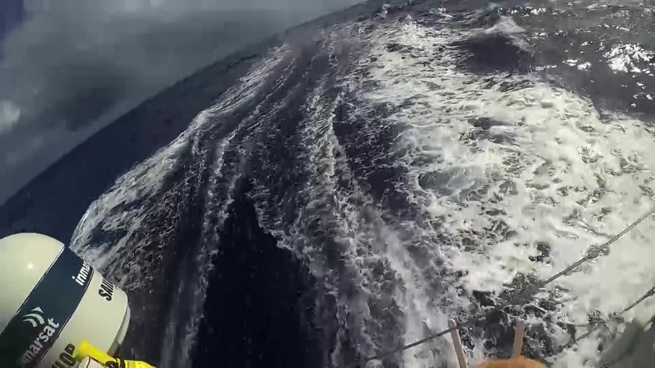 """GoPro view as Brian [Carlin] releases a drone on the stern. Drone shots of pulling away from Brian, then circling TTToP, triple-heading on port gybe. GoPro view of drone retrieval. Brian: """"Yeah. There we go."""""""