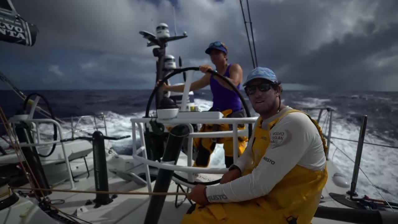 "Frederico, trimming, explains that they just gybed because they got an unexpected header, so they're now on course but on port insted of starboard. Liz steers. Drone shot with rain in the distance. Dee: ""Let's make this cloud our friend and stays with it."" Dee discusses strategy and nearby boats. ""We're in really light airs and just need a bit more oomph, really."""