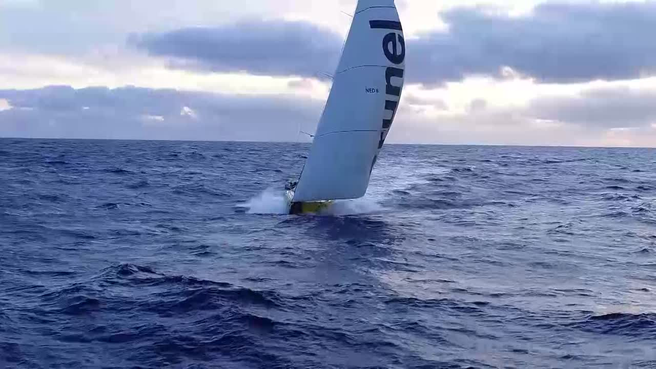 """Drone shots of Brunel sailing fast on starboard gybe, including washing-machine shots from the drone, with Yann on the stern. Drone recovery, I think by Bouwe, with Yann in the background at the controls. Sally, on the stern, says it's blowing 20-23 knots. """"Trying to get to Hong Kong."""" Bouwe trimming on the stern. Washing-machine shots of Jens in the cockpit. Abby and Sally sharing some kind of brightly colored candy from a ziploc bag. Below, Bouwe explains that yesterday they made a very good move breaking away from a cloud formation, and made good gains. Hopes they keep the breeze and make even more gains. Very nice sailing conditions right now; 48 hours from the finish. Strategy of how to get around the Phillippines is important."""