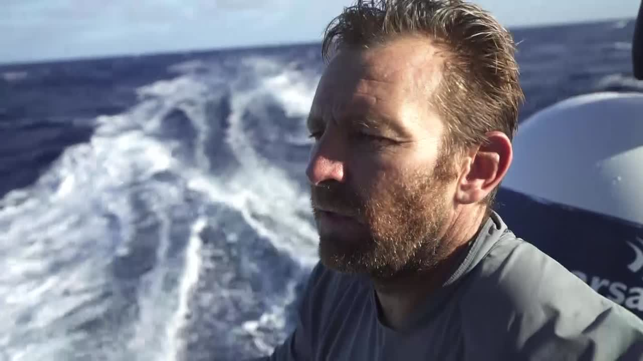 Very high drone shot. Jules, on the stern, talks about how they're in stealth mode. Most of those on the boat have done 35 out of the last 40 days at sea. Drone shot flying in toward and then past the boat.