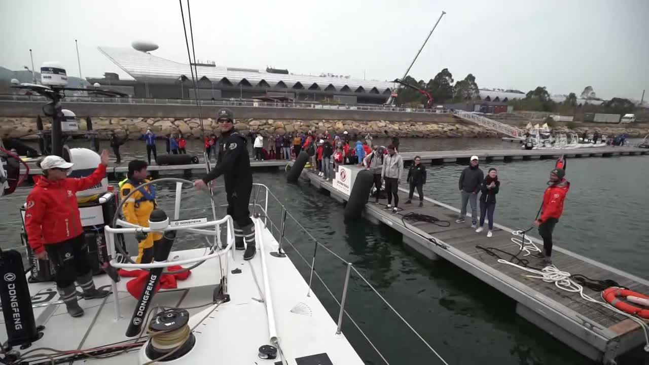 "Dongfeng docking out at the start of Leg 6. Black waves goodbye to the people on the dock. We see the MH0 being unfurled as Charles steers on the approach to the starting line. AkzoNobel is visible ahead of them and to leeward, the rest of the fleet to weather. Pascal with a tablet in his hand. Jérémie, after the start, looking forward at AkzoNobel and Brunel ahead of them. We see them furling the MH0 for a tack from port to starboard, then unfurling during a tack back to port. Charles: ""Nice one."" Pascal navigating. Their jumper going over. Kevin standing on the lifelines to do something to the clew of the MH0. Passing the leaving buoy. Later, they prepare to peel to the J1. Daryl: ""Put the sheet around the winch."" Bagging the lowered MH0 on the foredeck. Charles on the helm, talks about the start. Not so great in terms of their start, but good to have wind in exiting Hong Hong. Now at the back of the fleet. Daryl: ""Looking forward to sailing into Auckland. Probably 20 days away. Don't want to get too excited yet."" Jack, stacking on the foredeck, says pretty much the same thing. ""Long way to go though."""