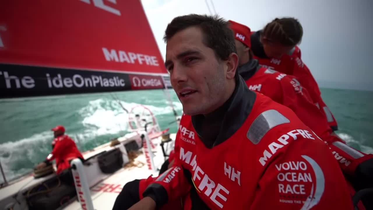 "Blair, on deck, talks about the start. Not the best start for them. Fourth now. Start not a huge priority in these conditions. Rough stuff in the next couple of hours. ""Feels like back home now; back on the boat. So it's all good."" Támara talks on deck in Spanish as they sail to weather under the J1. Looks like Scallywag is a quarter mile haed of them; I'm guessing that's Brunel beyond them. Then we go back in time and see the prestart, and the immediate start aftermath. Grinding, tacking out of Victoria Harbor. Close cross of Brunel behind them. Big duck of them to go astern of Dongfeng. Xabi trimming. Pablo on the helm. Rob calls for the hoist of the J1; we see it going up, then the furled MH0 coming down. Scallywag and Brunel sailing ahead of them and below, to starboard."