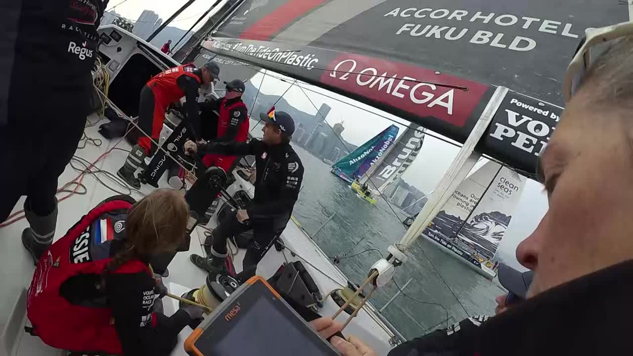 "Libby, wearing a GoPro (that really is a Garmin) in the prestart: ""20 to burn; 1:10 to go."" Witty, on the helm on the final approach to the line: ""Deploy the MH0 guys! When you're ready deploy the MH0. Go, go!"" Libby: ""No burn time."" We see the MH0 deploy. Libby: ""No burn time; we're late."" Close action as they're tacking out. Witty: ""Nice to wn the start in our home town."" Tacking out with other boats close. Slomo grinding. New crewmember Marcus talks excitedly about the good start. Marcus, grinding: ""I""m still feeling it. Didn't get much sleep on the plane, so I'll be looking forward to getting a bit of sleep tonight. I doubt it though."" He laughs. Libby on the LIbby-cam: ""J1 on the next tack."" António smiles in slomo. Witty steers."