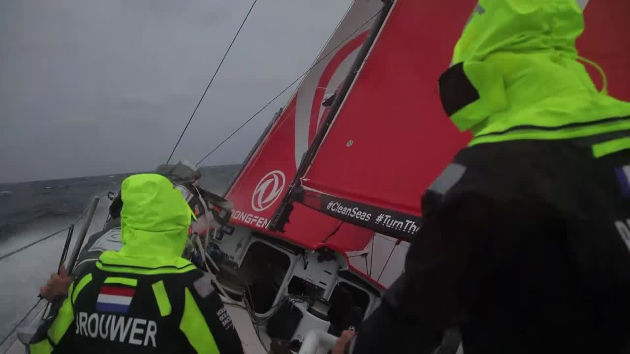 Sailing upwind on port in strong wind. Shots of other boats. Crew working the cockpit in spray. Bowcam shot of sail cahngin gon the foredeck in heavy spray. Bare-headed change from J1 to J2. Crew on the foredeck in night-vision shot gathering in the J1 as it comes down.