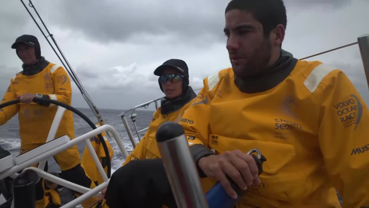 "Bernardo and Nicolas talk about being in the wind shadow of Taiwan. Francesca explains the wind reduction; quite shifty, just peeled to the J0. Can see the other boats quite close. Shot of two boats ahead of them. Nicolas talks about the wind. Brian, at the nav station, talks about the wind acceleration around the island. Got thorugh the first challenge, the monsoon wind between Hong Kong and Taiwan. Now in the lighter winds of Taiwan's wind shadow, but soon will be in the acceleration zone around the southern tip of Taiwan. Winds up to 30. Hope to get the J1 packed away, and the J2 and J3 ready. Going to be a bigger sea state, also. ""That's our challenge tonight. Then tomorrow should be better conditions."" Bernardo working on a bagged headsail; slomo of Lucas, Henry, and someone else in spray on the bow with competitor visible in the distance ahead of them."