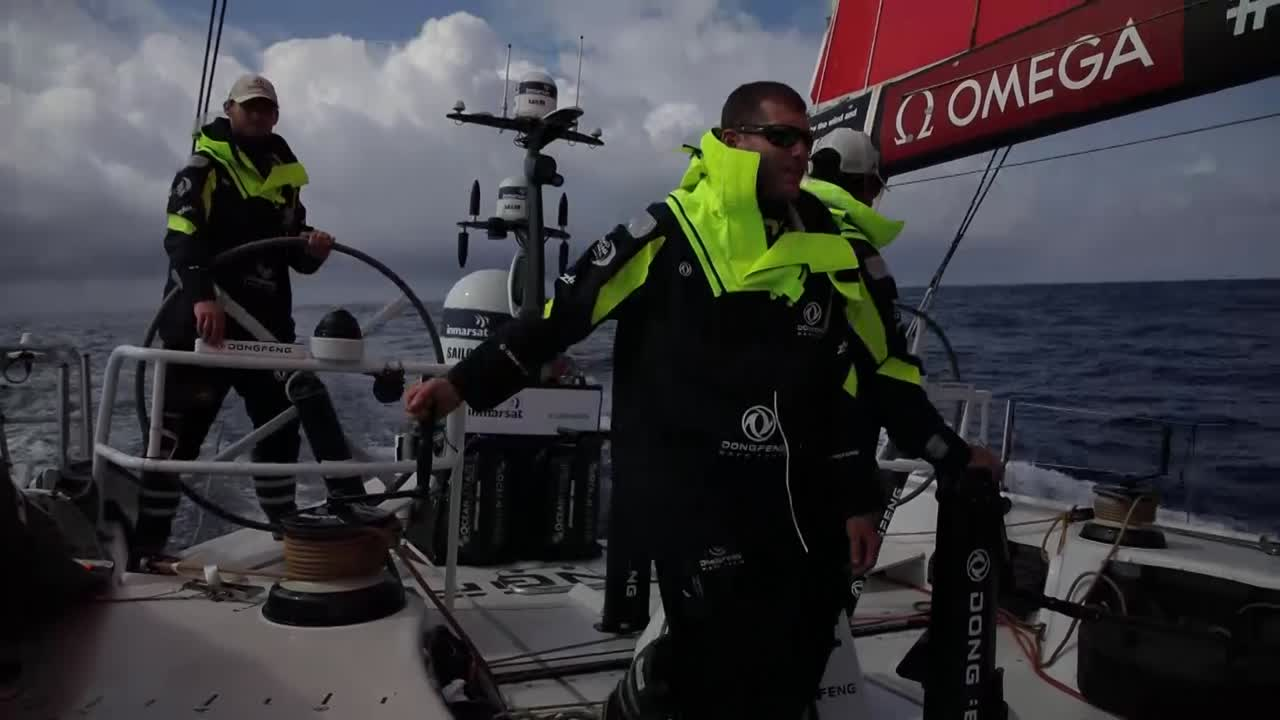 "In light winds they sail downwind. Charles calls below to rouse the off watch. Kevin gets dressed, goes on deck. Crew grinding in the cockpit as they peel to the MH0. Marie grinds, wearing a foulie top that says ""Liu"". Oops. Kevin on the bow lowering the old sail. A competitor (MAPFRE?) is visible ahead of them. Kevin eats. GoPro shot of him removing and clipping into a halyard, then he goes to the clew of the MH0. He attaches a new sheet, checks the leech line, and gives a thumbs up to Marie, who secures his line so he can pull himself back to the deck. ""Merci."" Below he takes off his foulies and gets back in his bunk."
