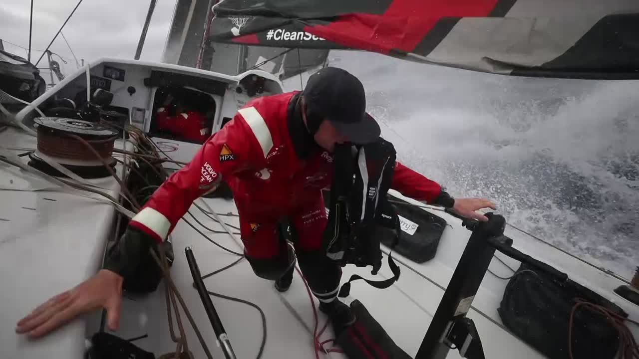 """Washing machine shot of cockpit. Slomo spray. Marcus, below, talks about how wet the boat is. """"I've never seen boats like this. They are just So. Wet. It's epic. It's good fun though. Nonstop spray in your face; no reprieve."""" Fish, below, talks about fast sailing. Slomo spray on deck. More spray. Annemieke talks about holding on, it's pretty bumpy. Slomo spray washing over Annemieke. Alex at the nav station, with Libby behind him, makes a wrap with a tortilla and something in it. """"It's almost like normal food."""" To Libby: """"Cutting the corner again."""" Witty talks about food, mangoes. Libby talks about how the northern group will get into some lighter winds and they'll be able to close some distance. Shots of nav software. Fish: """"It's all to play for. Like we saw in the last leg going the other way."""" The nav team is pretty happy with where they are and where they're going, and he has every confidence in them."""