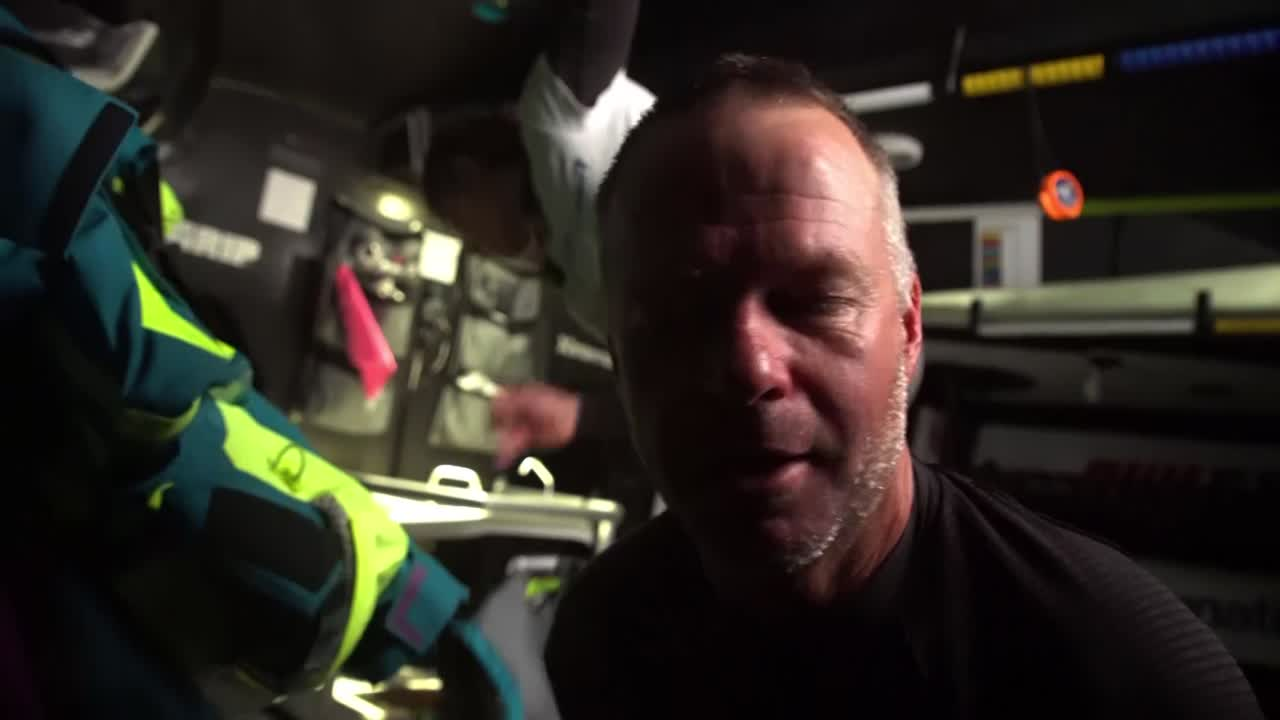 "Nicho, below, talks about how cool it was last night pushing in 28 knots of wind. Can't talk on deck; just focus on your job. When the front that they're on breaks down there will hopefully be some compression. Pressure on the team, and has been since they damaged the mast in Leg 3. He thinks they're a better team than where they're sitting overall. Nicolai, below, talks about Simeon getting blown off the wheel, making a big bang. ""Only one thing can make a bang that big, and that's him falling off the wheel."" He just ran for the wheel and grabbed it. Crash cam footage of the incident. Simeon: ""Reminds me of when I fall out of a tree as a young boy."" At the nav station, Jules talks to Nicho about Dongfeng doing a peel; maybe that's why they fell back. Nicho: ""We're just quick Jules."" Jules: ""The other two are quicker."" Nicho laughs. Washing machine shots on deck, closeup of the rudder. Cool fisheye perspective shots. Stacking, shot from outside the lifelines with a GoPro on a pole. Slomo washing machine. Spray. Brad grinding. Someone (Luke?) gives a thumbs up. ""Finally moving!"""