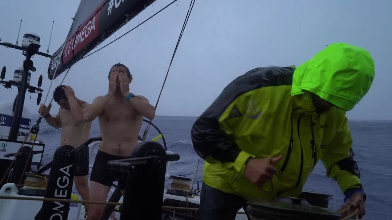 "Rain in the cockpit; crew showering. Alberto is very happy, after a week. Grinding for a sail change. Sailing upwind. Carlo fiddles with a pedestal. Below, he and Kyle inspect the pedestal, which is broken. Kyle explains that the pedestal started slipping. To fix it they've had to pull the pedestal apart, requires coordination with the guys on deck. Found the issue, which was a chip in one of the sprockets. So he's shaved that down, and will put it back in place in the position of the pedestal that they don't often use. Carlo works n the sprocket. Lubing the chain. Kyle: I've seen a lot of people do this stuff, but I haven't done it much myself. On deck, Louis comes up to report on a very good sched. ""Only 2,500 miles to go."" They flp in little wind. Below, Kyle works on putting the pedestal back together. Coordinates with Carlo on deck. ""Just be a bit rough with it, Carlo."" Kyle: ""Done."""