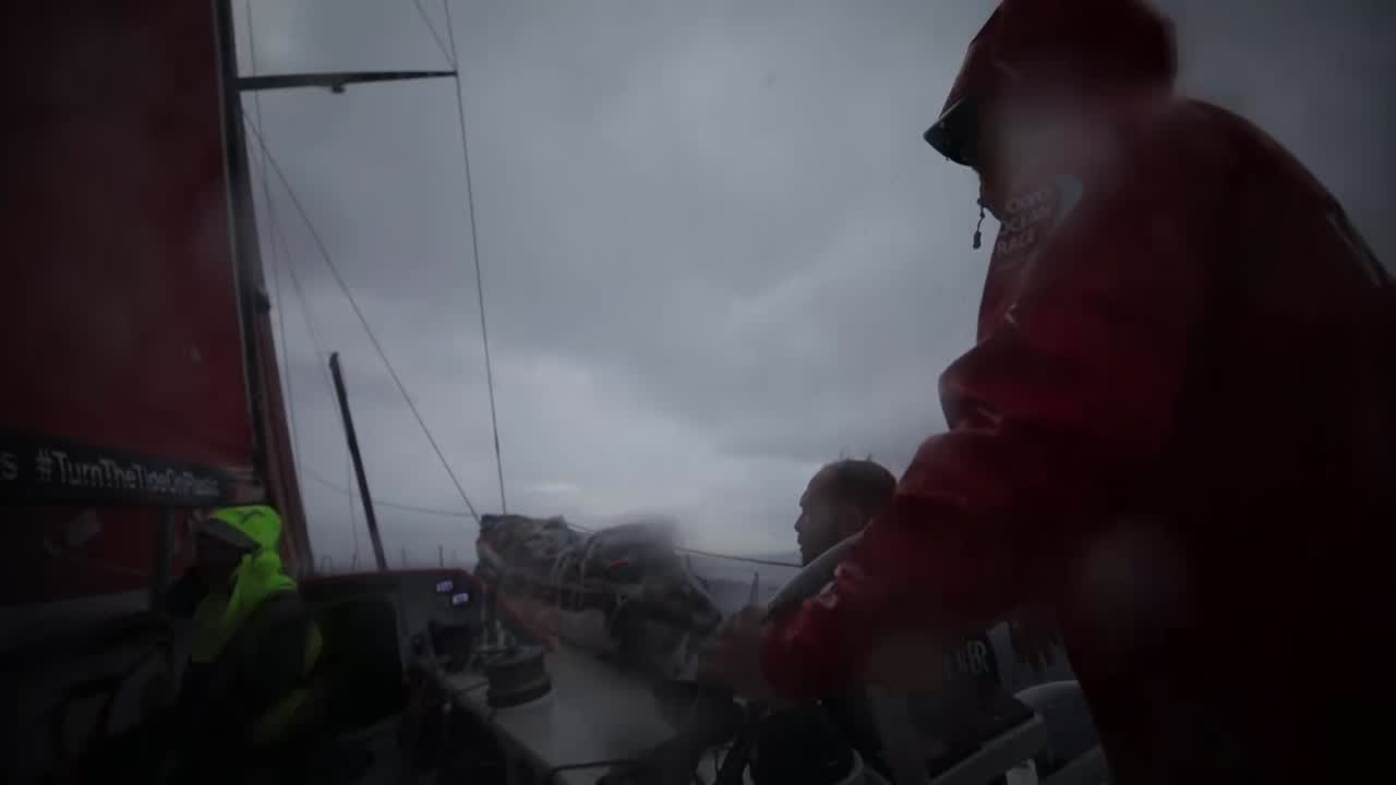 "Rain falling on deck. GoPro (Garmin) view as Kevin (I think) helps grind. Black trims the main as darkness falls. Kevin on the helm. Black explains how the wind pressure has dropped. Behind him, on the helm, Kevin is shouting to someone in French. Stacking with sunset clouds behind them. Carolijn explains how they're sailing in about 15 knots. Rain behind them. Traveling in the right direction now. ""Life's good."" Charles: Nearly last, with MAPFRE... I think we deserve it. The leg is still very long. Very complicated; there's still hope. Reduce the gap to the leader and maybe have an opportunity. Who knows what's going to happen in the doldrums. Kevin steers in the sunset, wearing Charles' jacket. (sigh. making my life difficult.)"