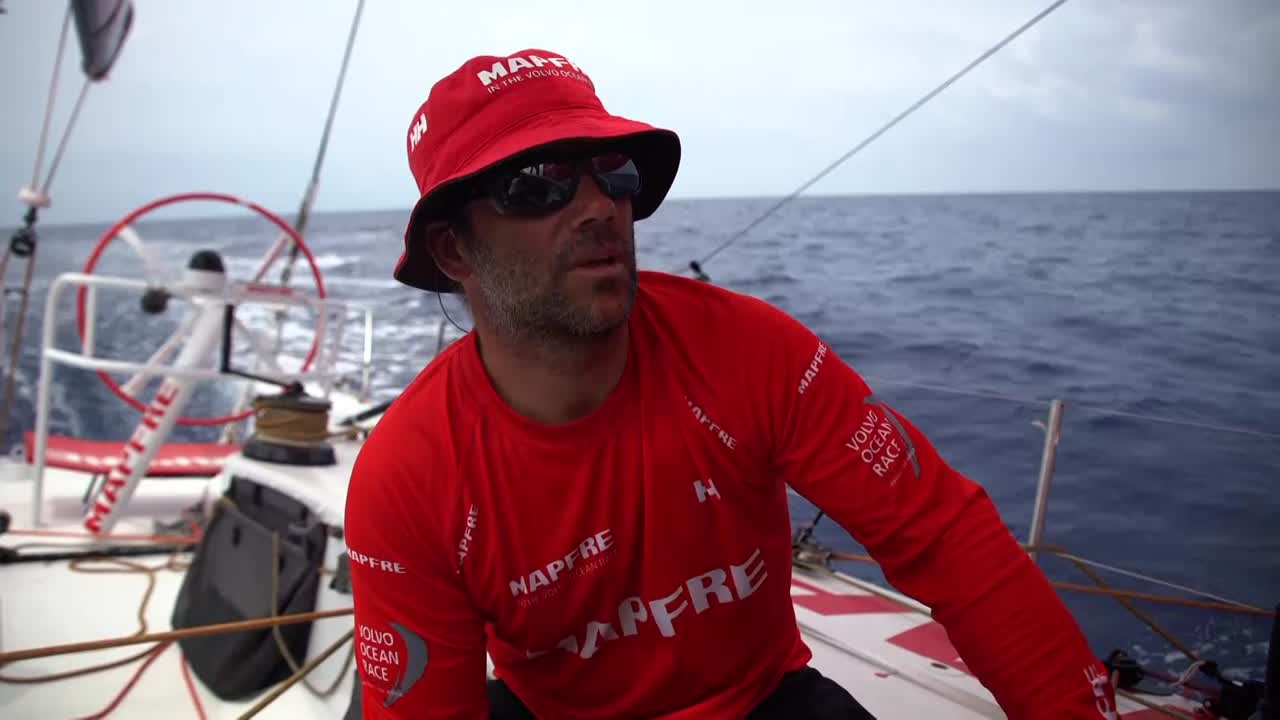 Pablo, in the cockpit, talks in Spanish about the competition. Rob gives a recap: heading southeast through the monsoon. Westerly breeze, big clouds, 10-30 knots of wind with big direction changes. A lot of work. They're a day behind the fleet. Giving it their best shot. Dongfeng on the bow. Fingers crossed we'll see AkzoNobel again before Auckland. Xabi looking through binoculars. Louis on the clew. Easing sails in a squall. Slomo spray on the bow. Blair and Willy grinding in slomo. Grinding in a squall. Rain clouds. Slomo rain. Tamara makes the shaka sign.