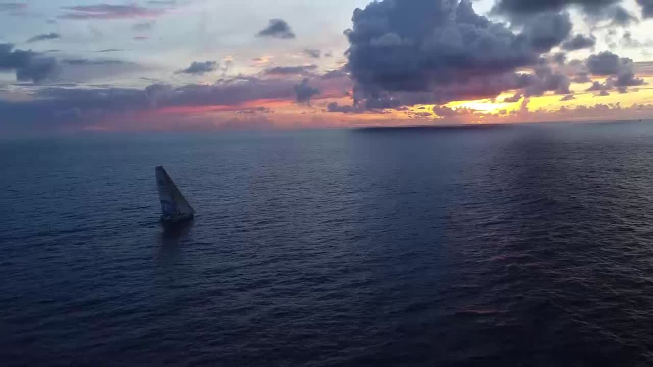 "Beautiful sunrise drone shots. Dee points out Brunel on the horizon ahead of them. Brian talks about how they've held onto Brunel, and gained ground on Dongfeng and MAPFRE behind them. Closing in on Brunel. Drone shot showing both boats in light air, with rain cloud in the distance. Drifting conditions with Brunel a few hundred yards off their bow. Nicolas talks with Brian as Brunel drifts a hundred yards off their starboard beam. Brunel falling behind them, then just ahead of them. Dee, on the helm, about how it's crazy to sail three and a half thousand miles and be side-by-side with their buddies. Suddenly wind is ahead of them. They cross Brunel on port, with Liz giving a ""woo hoo!"" on the helm. Lucas talks about how good it was to gain and cross ahead of them. Brunel crossing behind them. They wave."
