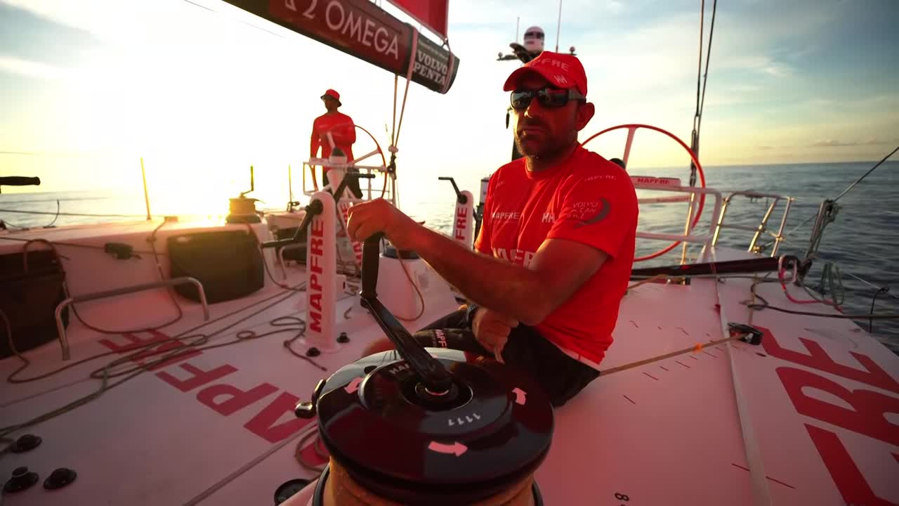 Xabi, trimming in light air, talks about the close competition with Dongfeng. Sunset. Xabi talks in Spanish. Pretty drone shots of sunrise with Dongfeng on the horizon. Tacking the MH0 with Dongfeng 2 miles ahead of them. Dongfeng behind them. Crossing Dongfeng a half mile ahead of them. Sunset shots with Dongfeng.