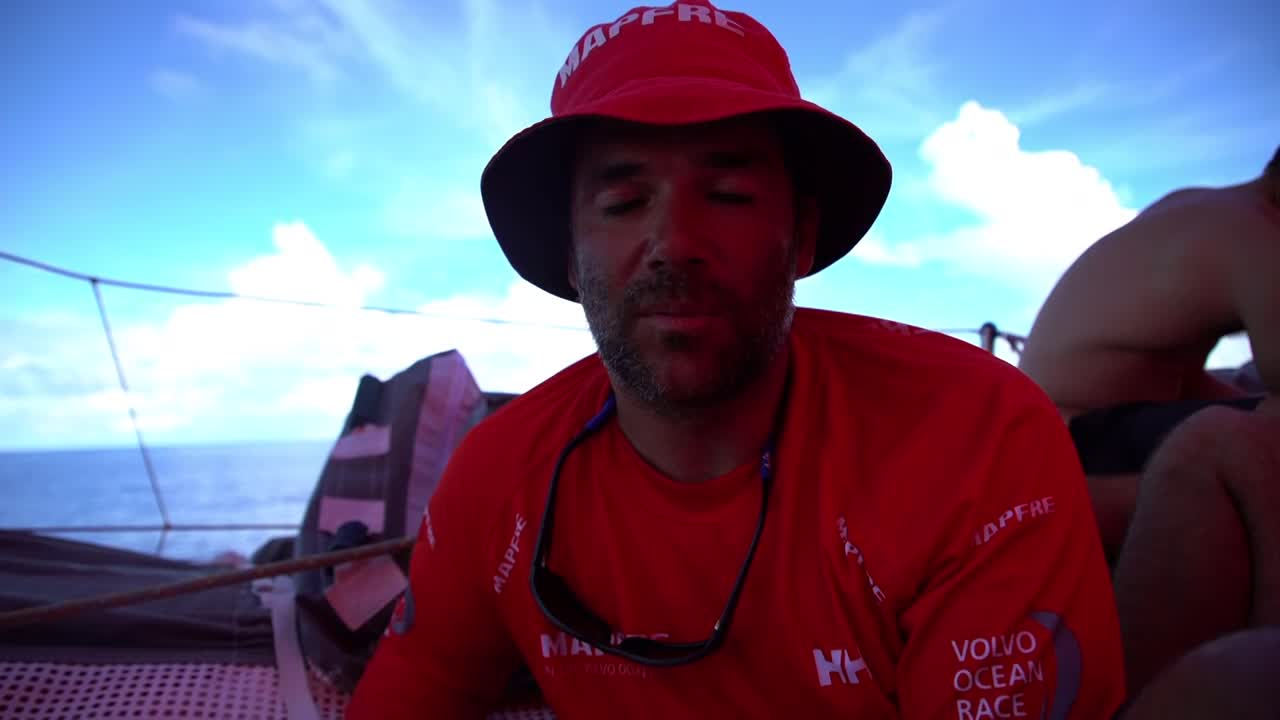 "Pablo talks in Spanish on deck. Drifting in glassy conditions with huge clouds in the distance. The keel. Dongfeng sailing about two boatlenghts away to weather. Dongfeng rolls them. Sophie on the bow. ""I think they were quite happy to pass us. We are officially last."" She waves to them. Blair and Xabi trim while watching them. Then Dongfeng is behind them again, yay! Drone shots of the two boats sailing a few boatlengths apart."