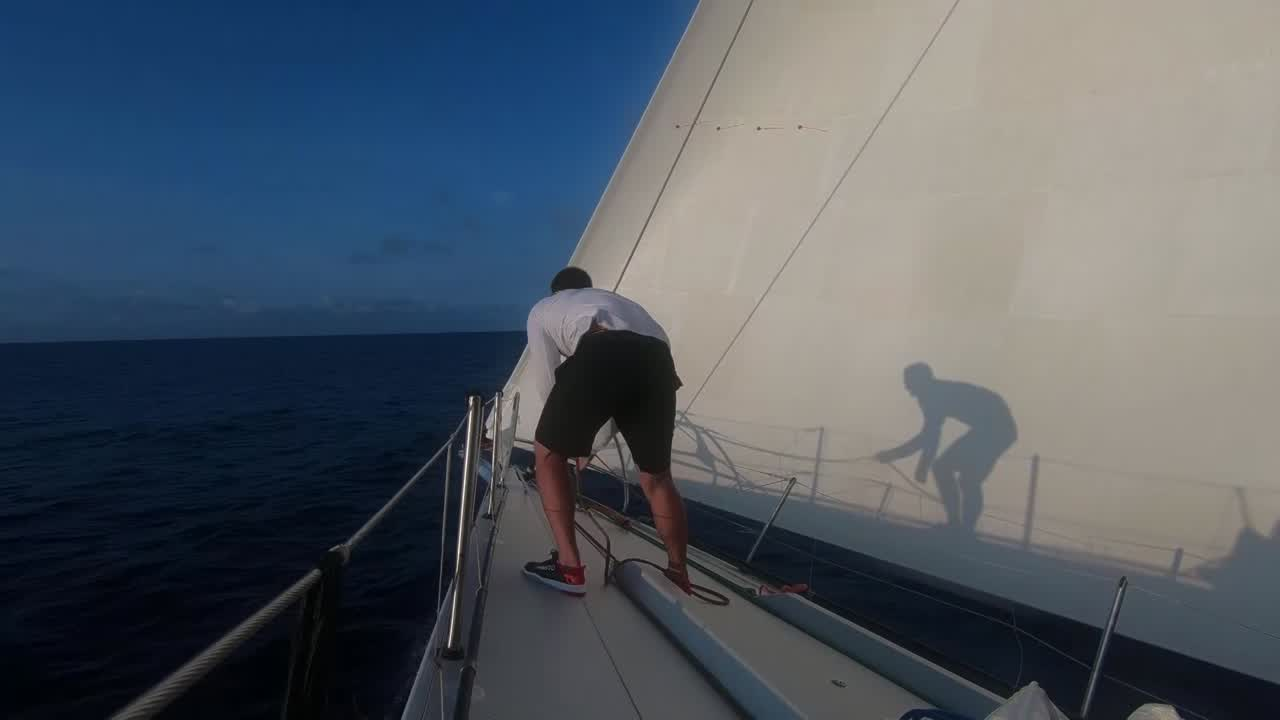 "Lucas: ""This morning I was up in the bow, tidying up a bit, and he just thought it was a time to clown around. Do some dancing."" We then see a special effects shot of Lucas tidying a line on the bow while his shadow, on the MH0, is dancing. Cute! ""Crazy. We've got a race to win here."""