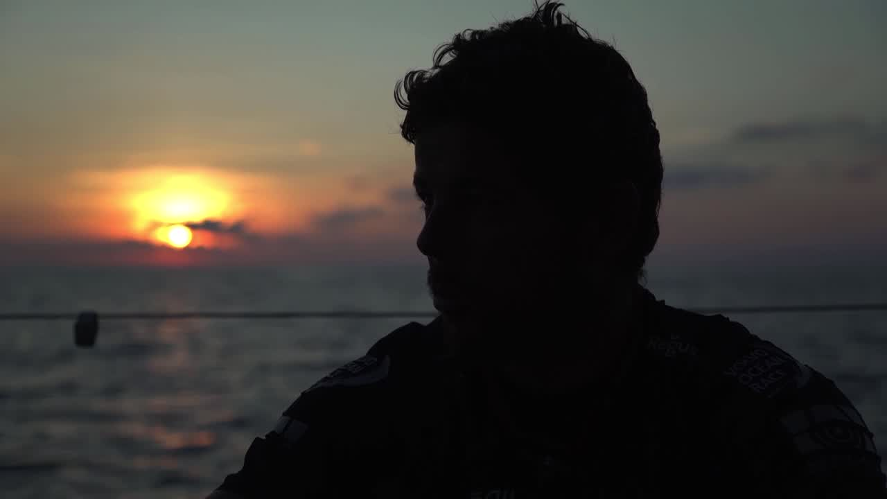 Sunrise. Crew talks about Akzo being 6 miles north of us. Foredeck. Crew smiling. Morale seems good. Fish on the helm. Just a lot of cool shots without a lot of dialog; just the crew being happy, moving well. Relaxed.
