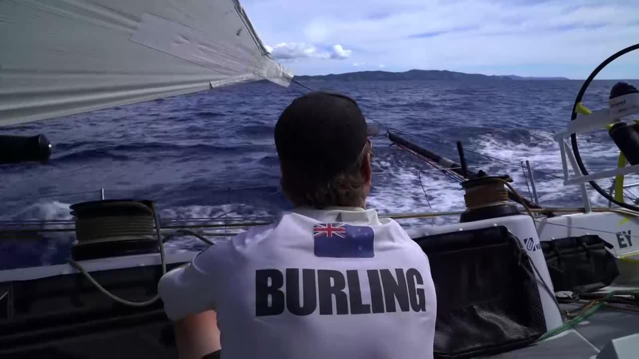 Sailing along the coast of New Zealand. Peter looks at the shore. Peter steers.