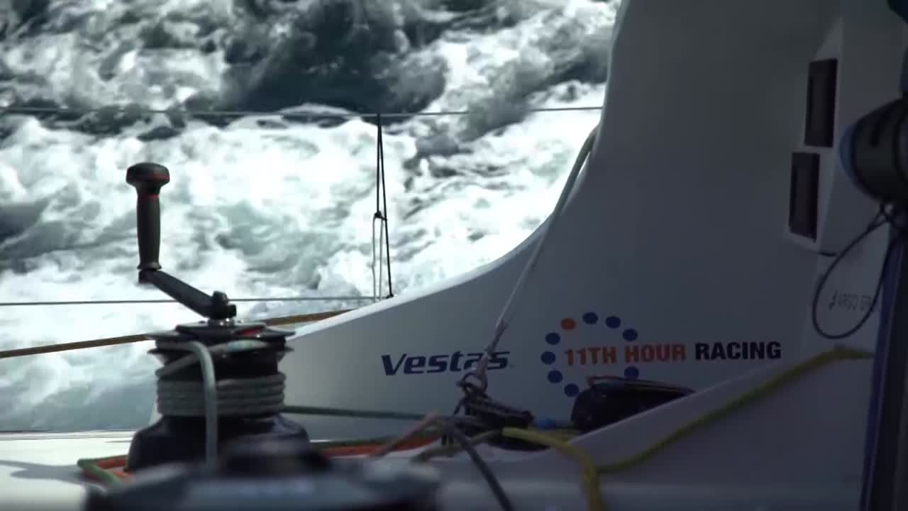 "Drone shot of Vestas sailing upwind in 15-knot conditions. Double-heading with J0 and J3, it looks like. Charlie in the cockpit: Good to get back on the water. A little on the back foot, but they'll grind it out. Shot looking forward as the VOR-hired helicopter hovers at low altitude, shooting back toward them. Mark: Lots of anticipation, repair. But the day's finally here. Charlie: All or nothing until the next leg. Vestas sails toward shore with Phil on the helm. Mark: Just gonna have to out work all these other guys. SiFi at the nav station. It's father's day today in Spain, so I have a few little pictures from my boys. Leopard, dragon, dolphin, hippo. Made my day at least. It's the thing I miss the most when I'm away. They're beginning to understand that I'll be away for a few weeks. Nick in the hold swapping a spare electrical panel for the engine; got some water into it. ""This isn't a tough thing to solve; it's just annoying."" High drone shot with a competitor behind them in the distance."